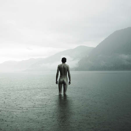 Picturesque landscape. Young naked man in lake
