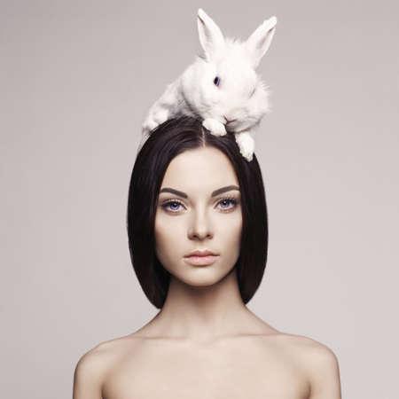 Photo pour Studio fashion portrait of beautiful lady with white rabbit - image libre de droit
