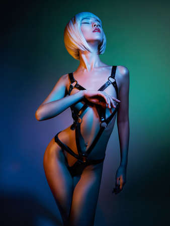 Photo pour sexy young woman in erotic fetish wear dancing striptease in nightclub. Beautiful nude body of sensuality elegant lady. - image libre de droit