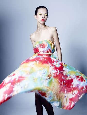 Photo pour Fashion studio portrait of beautiful woman in azure flowing dress on colorful background. Asian beauty. - image libre de droit