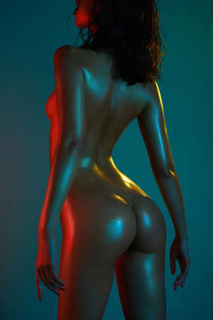 fashion art photo of elegant nude model in the light colored spotlights. Neon light filters on naked body of dancing girl. Sexy woman in night club show striptease. sexual pose of young lady.