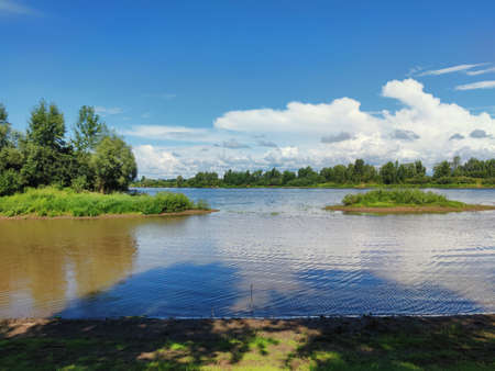 Photo pour green islets on the river against the background of blue sky with clouds on a sunny day - image libre de droit