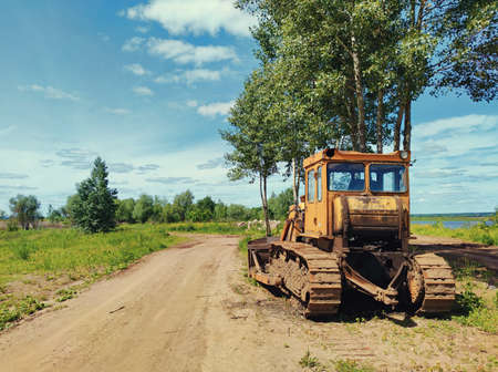 Photo for yellow tractor bulldozer stands on the side of a country road in the village against a beautiful blue sky on a sunny day - Royalty Free Image
