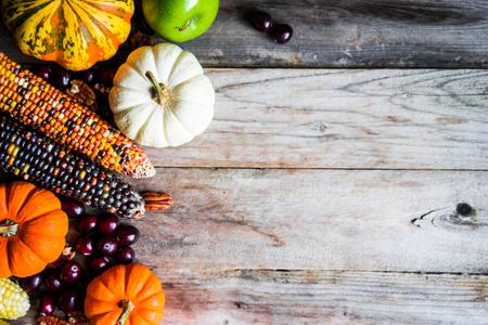 Photo pour Pumpkins,corn,apples,nuts and cranberries on wooden background - image libre de droit