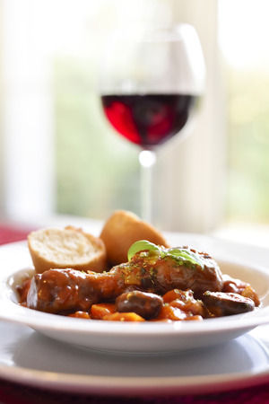 Coq au vin, french cuisine. Chicken leg with red wine and tomato sauce with vegetable on bread on a wooden table.
