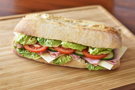 Delicious ciabatta sandwich with ham, tomatoes, fresh salad and cucumber slices.