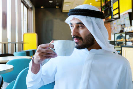 Photo pour Close up of Arab man drinking coffee inside a cafe shop looking far outside through the window - image libre de droit