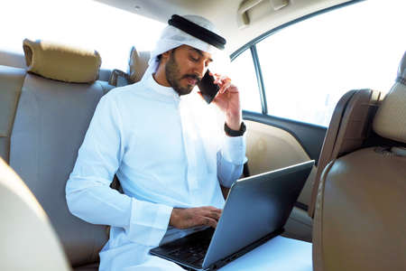 Photo pour Arab business man talking to a bank representative while performing online banking through his electronic devices - mobile phone and laptop - image libre de droit