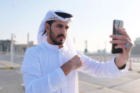 Photo pour Middle Eastern Emirati Arab model fixing his traditional menswear garment Ghutra using his phone - image libre de droit