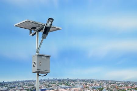 Photo pour Solar panel lighting pole with cityscape with blue sky and white clouds. Renewable Energy concept. - image libre de droit