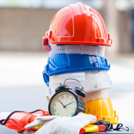 Photo pour Stack of engineer safety helmets with construction area blueprint, black alarm clock with cotton gloves lay on nearly working area. - image libre de droit