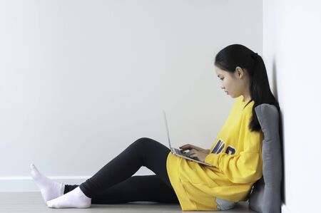 Coronavirus crisis, Asian female teenager use 18 years old do online learning from home by laptop, woman wearing casual yellow cloth use laptop for work from home during corona virus crisis. Thailand.