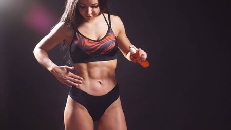 Photo pour Girl with a beautiful toned figure, muscular body, uses body oil, isolated background. - image libre de droit
