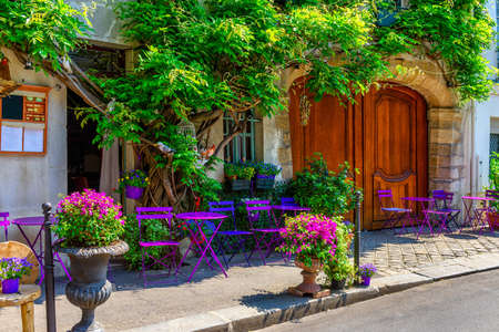 Foto de Cozy street with flowers and tables of cafe  in Paris, France - Imagen libre de derechos