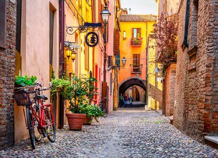 Foto de Cozy narrow street in Ferrara, Emilia-Romagna, Italy. Ferrara is capital of the Province of Ferrara - Imagen libre de derechos