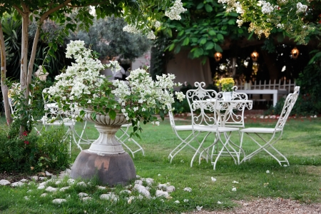 White table and chairs in beautiful garden