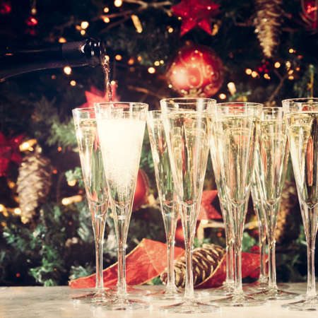 Filling up glasses for party. Many glasses of champagne with Christmas tree background. Party setup. Holiday season background. Traditional red and green Christmas decoration with lights. Holiday party. Square