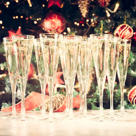 Many glasses of champagne with Christmas tree background. Party setup. Holiday season background. Traditional red and green Christmas decoration with lights. Holiday party. Square