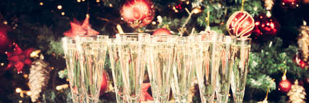 Many glasses of champagne with Christmas tree background. Party setup. Holiday season background. Traditional red and green Christmas decoration with lights. Holiday party. Horizontal