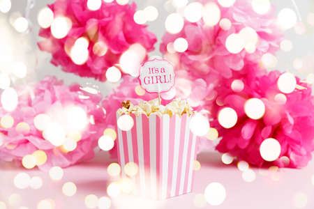 Photo pour Its a girl sign in a popcorn bag at the baby shower party. Paper flowers background. Baby shower celebration concept. Festive party background. Horizontal with festive holiday bokeh - image libre de droit