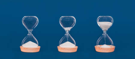 Photo pour Hourglasses with increasing amount of sand. Concept of time and timely actions, time management and growth mindset. Banner format - image libre de droit