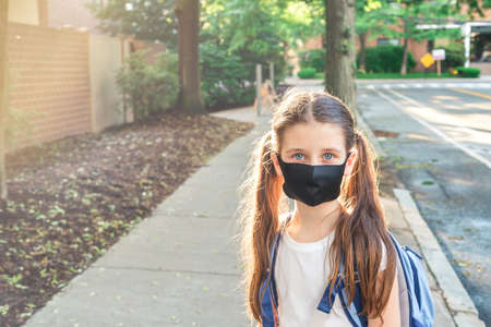 Foto de Elementary school student in a cloth dust mask with backpack in the street. Preteen girl is going to school in new normal. Education, coronavirus, back to school concept - Imagen libre de derechos