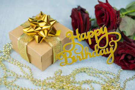 Foto de greeting card happy birthday birthday with bouquet of roses red gift box surprise with gold bow with text and inscription - Imagen libre de derechos