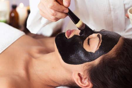 Photo pour Beautiful woman with facial mask at beauty salon. Spa treatment - image libre de droit