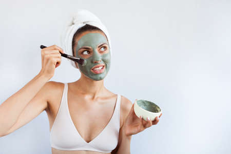 Young beautiful woman in face mask of therapeutic blue mud. Spa treatment, self care and healthy skin. Copy space, white backgroundの写真素材