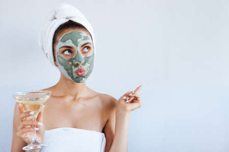 Young beautiful woman in face mask of therapeutic blue mud with champagne. Spa treatment, self care and healthy skin. Copy space, white backgroundの写真素材