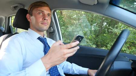 A male businessman in a shirt and tie is driving a car and browsing the message on his phone. violation of traffic rules.
