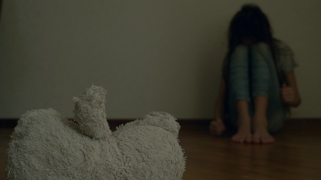 Photo pour a desperate child in depression sits at the wall of his room, tries to attempt suicide. next to it is an abandoned soft toy - image libre de droit