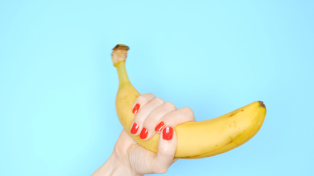 Photo for female hands with red nails are holding a yellow banana on a blue background. - Royalty Free Image