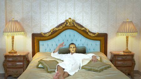 Handsome man in a golden mask and a bathrobe is resting on a luxurious bed. looking at the camera