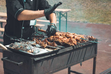 Photo pour Chef is cooking outdoor grilled meat on skewers, shish kebab,shashlik quails,vegetables, on a brazier. Roasted meat cooked at barbecue. Heat from the fire. - image libre de droit