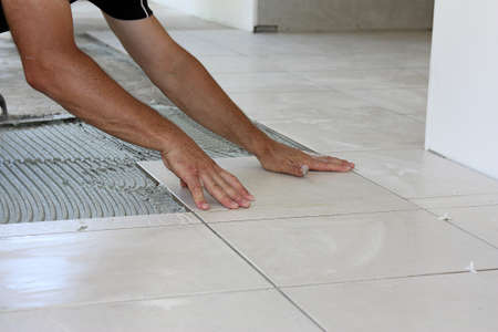 a male tiler laying light color floor tiles