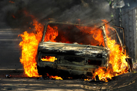 Photo for Delivery type vehicle on side of road burning with large flames and smoke. Car fire on desert rural road. Car on fire after and accident or during a riot. - Royalty Free Image