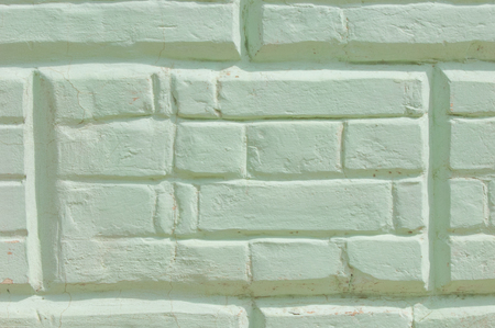 Texture, background, pattern. The brick is laid out decoratively. Brickwork, painted. Old brick wall with white and blue brick background. Ancient brick wall