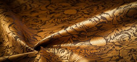 Photo for embossed pattern, composite textile, silk fabric of yellow, gold color, with a floral pattern, unusually pleasant visual sensations: slippery, coolness, softness; beautiful appearance, unique shine; - Royalty Free Image