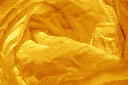 Photo for Texture, background, pattern, silk fabric, yellow, layered lace tulle, premium plain winter diamond knitted scarf in the form of infinity loops - Royalty Free Image