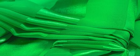 Foto de Texture, background, green silk striped fabric with a metallic sheen. If you have a bad mood, this fabric will lift it to unprecedented heights. Your project will be successful. - Imagen libre de derechos