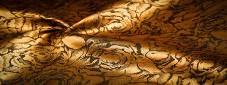 Photo for silk fabric with flower pattern, dark yellow, golden color, unique shine, embossed pattern, composite textile. relief pattern - Royalty Free Image