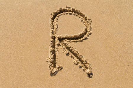Letter R of the alphabet written on sand with upper case.