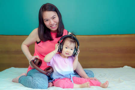 Foto de A beautiful Asian lady mother is pregnant. Take a big headset Come to the stomach Let the child in the belly listen Have a little daughter playing beside happily - Imagen libre de derechos