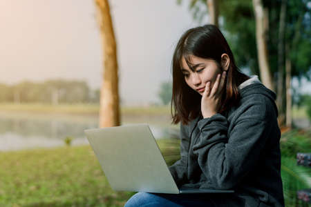 A lovely Asian girl is bright in the tourist area. There is a laptop computer in the hand on the road amid the fog. The back is a lake Sitting looking at the computer screen, working smiling happily