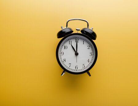 Photo pour Alarm clock on yellow background top view. Concept of time - image libre de droit