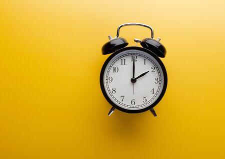 Photo pour Alarm clock on yellow background top view. Concept of time. - image libre de droit