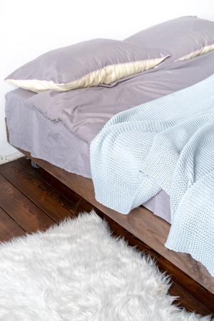 Photo pour Unmade bed with grey linen and fur rug - image libre de droit