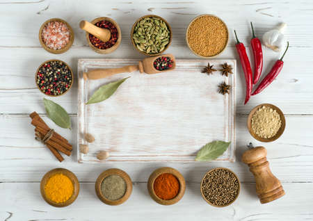 Photo for Set of various spices and herbs around an empty cutting board on white wooden background. Top view copy space. Flat lay - Royalty Free Image