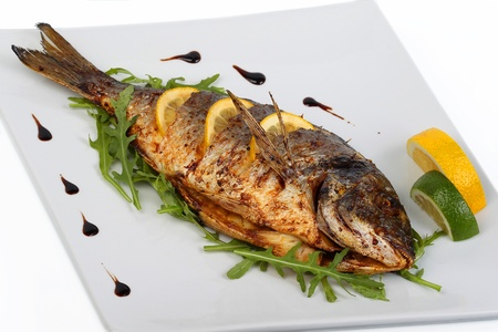Foto de fried fish with fresh herbs and lemon - Imagen libre de derechos